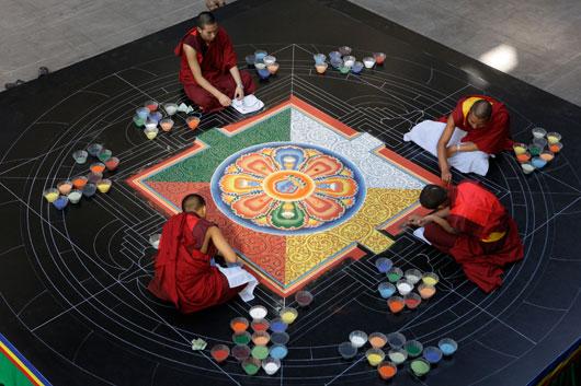 Mönche malen ein Sandmandala in der Jahrhunderthalle